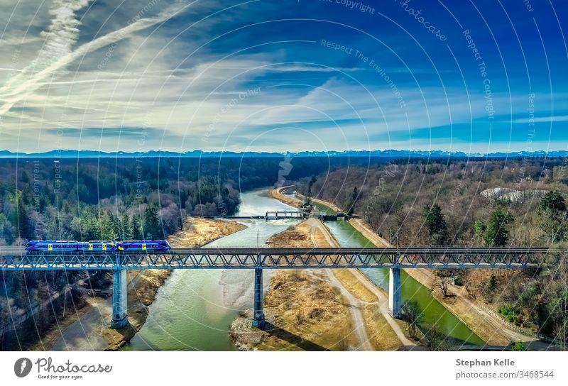 Ein Zug fährt über eine über einem Fluss gelegenen Eisenbahnbrücke mit Bergen im Hintergrund Brücke eisenbahn Verkehr Außenaufnahme Bahnfahren Landschaft Natur