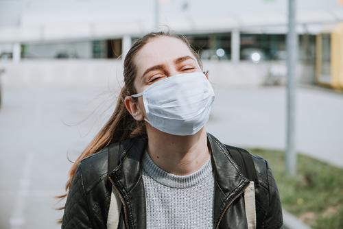 Junge Frau genießt die Sonne mit Maske zum Schutz vor Coronavirus covid-19 Air Atemschutzmaske blond Kaukasier Korona-Epidemie corona italy Corona-Virus dunkel