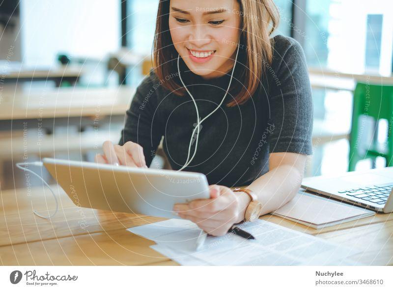 Junge lächelnde asiatische Geschäftsfrau, die im Büro oder Café Musik hört und Tablets benutzt, Lifestyle und Geschäftskonzept Business lässig heiter Großstadt