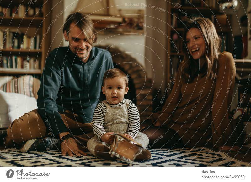 Junges glückliches Paar, das mit seinem kleinen Sohn zu Hause bleibt und auf dem Boden des Wohnzimmers sitzt. lieblich Fröhlichkeit Mann Frau Liebe heiter