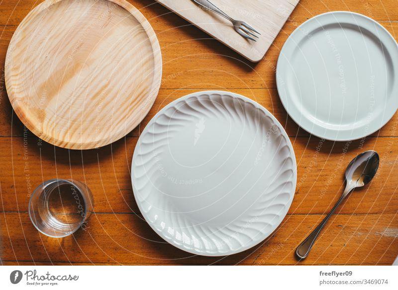 Flachlegen von drei Tellern und etwas Besteck Attrappe Flachlegung flache Verlegung Küche Holz Porzellan weiß hölzern Tisch von oben Zenital leer Koch