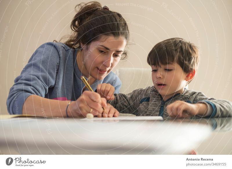 Mutter hilft kleinem Sohn bei den Hausaufgaben zu Hause Kinder Bildung heimwärts Frau Familie Muttertag Liebe schreiben unterrichtete 4s 30s
