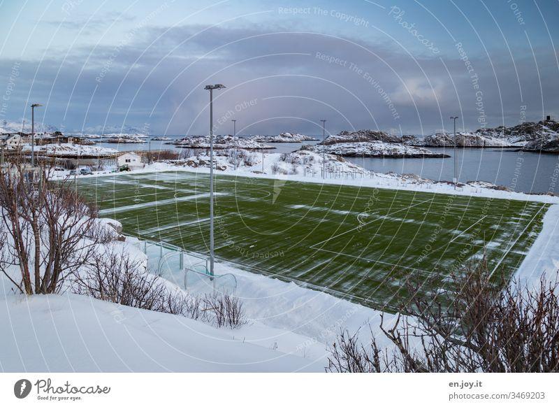grünes Fußballfeld auf einer Insel im Meer in Schneelandschaft Henningsvær Lofoten Norwegen Skandinavien Winter Sportplatz Kunstrasen Austvagoya