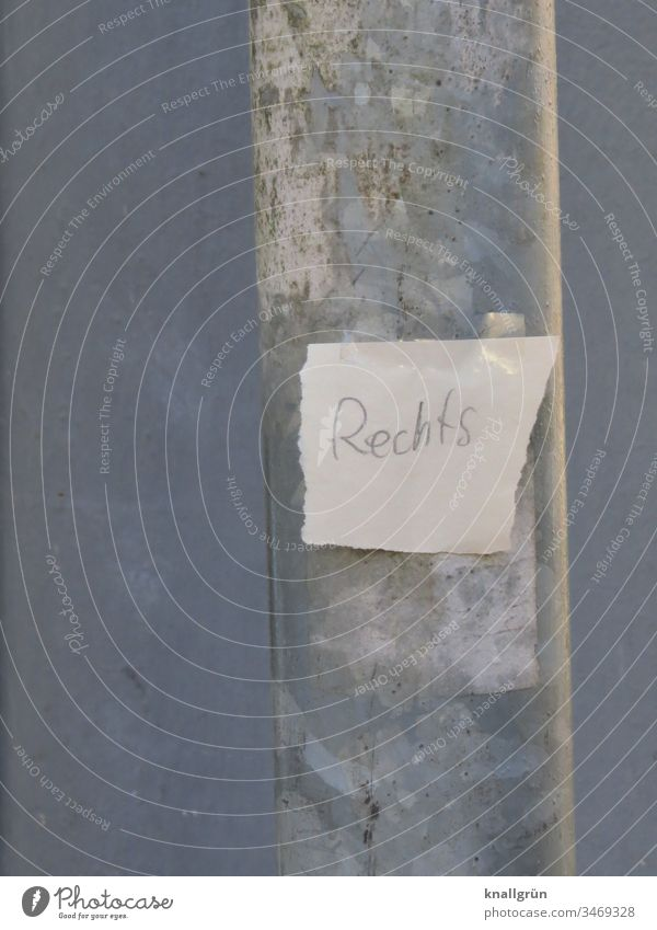 """Papierschnipsel mit der Aufschrift """"Rechts"""" mit zwei Stückchen Klebefilm an einen Laternenpfahl geklebt Zettel Wort Buchstaben abgerissen Schnipsel rechts"""