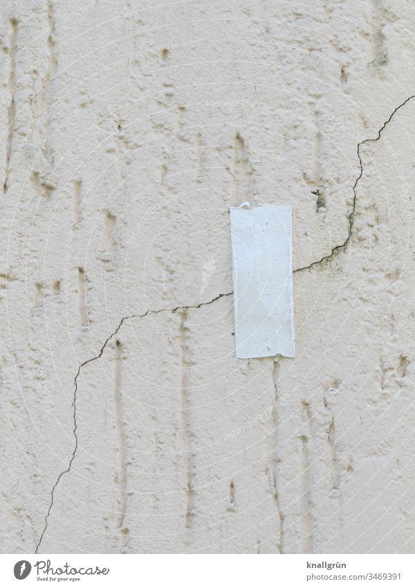 Ein Stück weißes Klebeband über einem Riss im Putz einer Hauswand Wand Schutz Mauer Fassade überklebt Rauputz Haarriss senkrecht Muster Strukturen & Formen