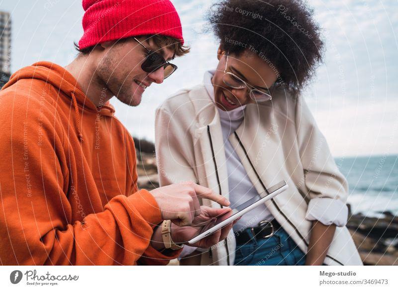 Zwei Freunde verwenden ein digitales Tablett. Tablette im Freien jung Spaß Frau heiter Lifestyle Technik & Technologie Freundschaft pc Zusammensein Stehen