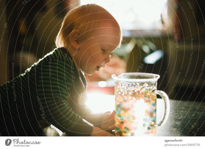 kleiner Junge entdeckt bunte Perlen Farbfoto Kind Porträt perlen Lichteffekt entdecken lernen erforschen Begeisterung Spielen Kindererziehung Kindheit Freude