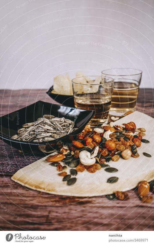 Mix aus Snacks mit Chips, Nüssen, Samen und Bier Aperitif Amuse-Gueule Lebensmittel dunkel helles Bier Muttern Studentenfutter Saatgut Mandeln Haselnüsse