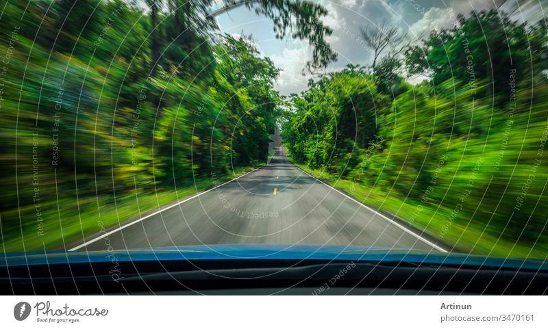Blick von vorne auf blaues Auto auf Asphaltstraße und Geschwindigkeitsunschärfe auf Autobahn im Sommer mit grünen Bäumen Wald auf dem Land abstrakt Kunst