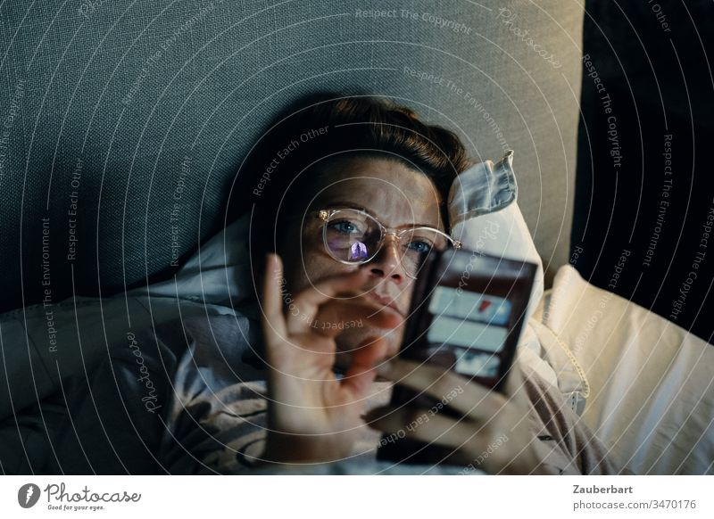 Frau schaut im Bett auf ihr Handy, schreibt und liest social media Brille lesen Kissen Morgen Lichtstimmung Internet Telefon SMS Kopfkissen gemütlich schreiben
