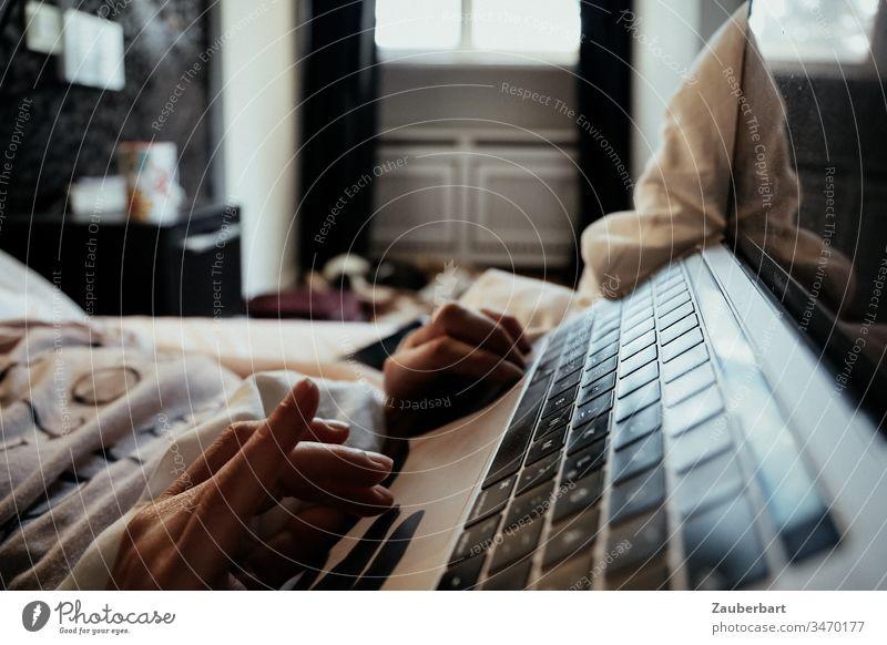 Tastatur eines Notebooks, Hand und Bettdecke, morgens im Schlafzimmer Homeoffice stayhome Morgen Fenster Lifestyle Technik & Technologie Computer