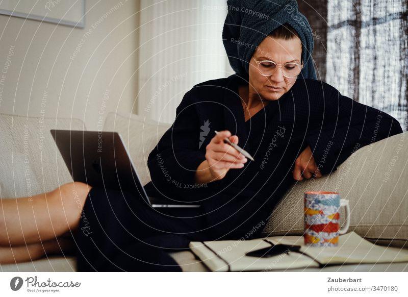 Schöne Frau im Bademantel sitzt mit Laptop, Stift und Notizbuch im Homeoffice auf der Couch stayhome Tasse Kaffeetasse Notebook sitzen arbeiten Notizen Computer