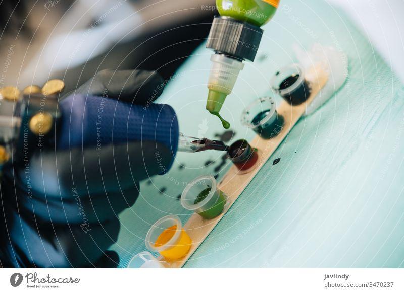 Tätowiererin, die die Tätowiermaschine mit Tinte belädt. Tattoo Maschine Tusche Farbstoffe Tätowierung Atelier Mischung Frau schön Mädchen organisch Werkstatt