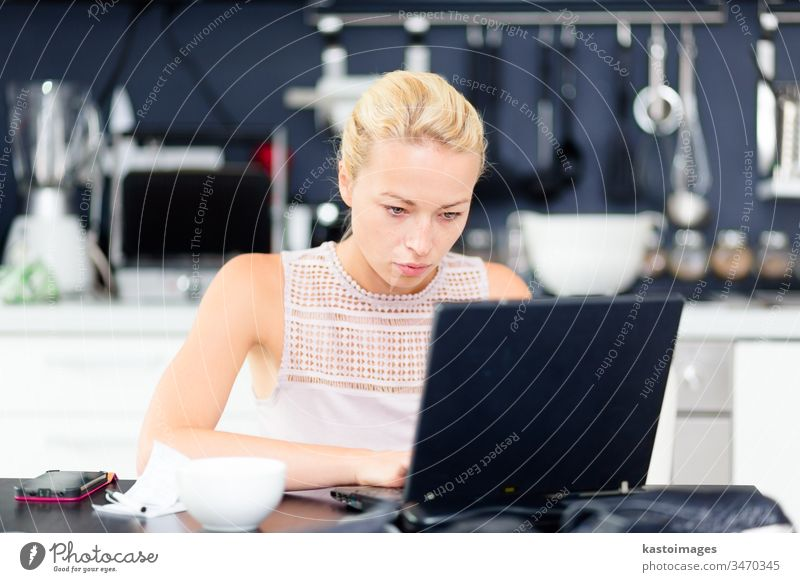 Geschäftsfrau, die von zu Hause aus arbeitet. Multitasking Arbeit heimwärts lässig Morgen Heimarbeitsplatz Kaffee Küche Smarth-Telefon Manage Business Büro
