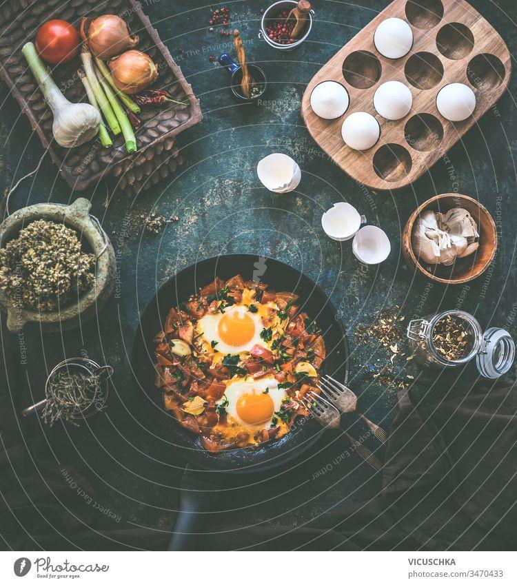 Schmackhafte Spiegeleier in Tomatensauce in schwarzer Pfanne mit Gabel auf rustikalem Hintergrund. Ansicht von oben. Shakshuka-Frühstück. Die Zutaten. Kochen. Gesunde Ernährung
