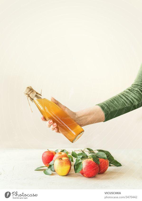 Weibliche Frauen halten eine Flasche mit hausgemachtem Apfelessig in der Hand über einem Tisch mit Äpfeln und grünen Blättern vor weißem Wandhintergrund. Apfelsaison. Konzept für gesundes fermentiertes Essen