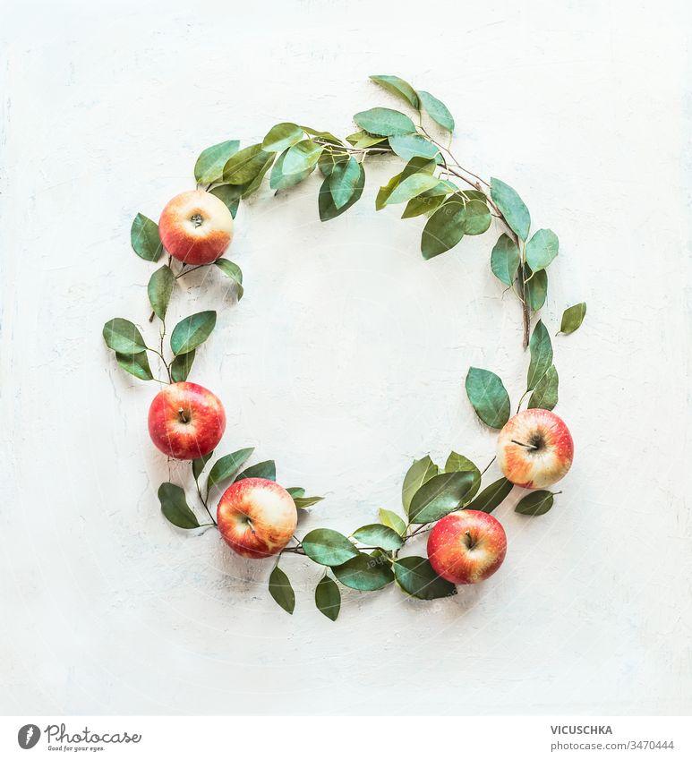 Schöner Kreisrahmen aus Äpfeln und grünen Blättern auf weißem Hintergrund. Kranz aus Früchten. Ernten . Apfel-Saison schön kreisen Rahmen gemacht Totenkranz