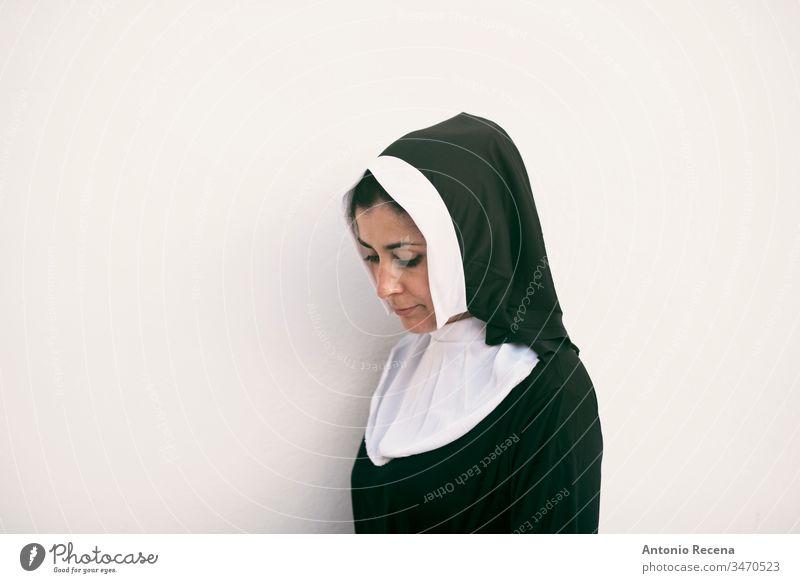 Nonne auf weißem Hintergrund mit Blick nach unten ernst Frau Religion Habitus Katholizismus 30s 40s Tracht Klischee hübsch attraktiv weißer Hintergrund