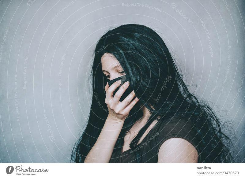 Traurige Frau mit schwarzer Gesichtsmaske COVID Bund 19 Corona-Virus Mundschutz Operationsmaske schützend Schutz Krankheit Infektion ansteckend Hand Trauer