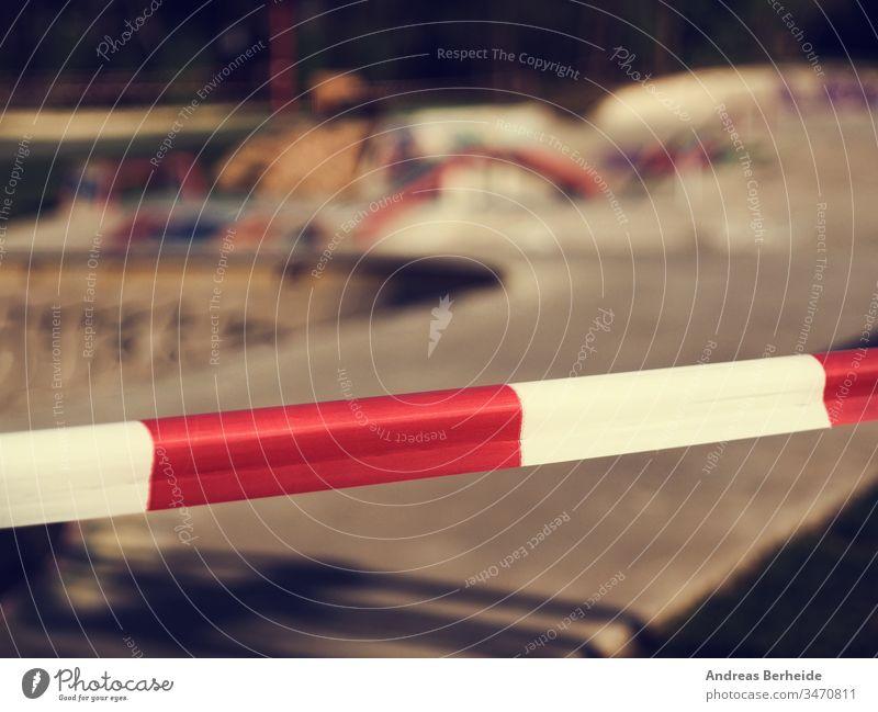 Nahaufnahme des Absperrbandes vor einem Skatepark, zu Hause bleiben, leeres Stadtleben Korona Virus Schloss Ausfahrt covid-19 Aufenthalt Klebeband Barriere Park