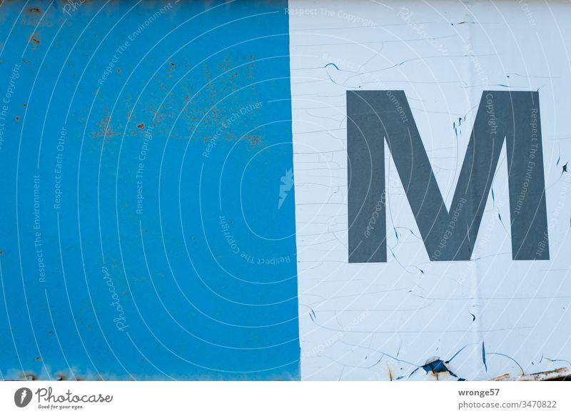 """Großbuchstabe M auf weißem Folie an einem blauen Tor Buchstaben Farbfoto Tag Schriftzeichen Außenaufnahme Gebäude Orientierung alt verwitterte Oberfläche,"""""""