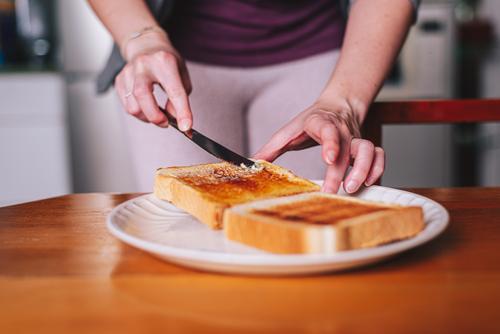 zwei Hände, die Butter auf Toast streichen sich[Akk] ausbreitend Zuprosten Teller Frühstück Messer Lebensmittel Küche Morgen Mahlzeit Margarine verbreitern