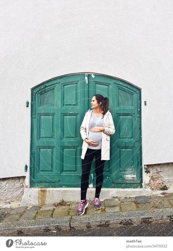 Junge schwangere Frau vor grüner Tür Schwanger Jugend Grün Babybauch