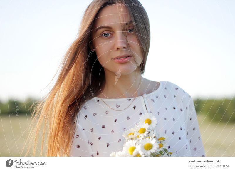 Schöne junge Frau genießt Gänseblümchenfeld, schönes Mädchen entspannt sich im Freien, hat Spaß, hält Gänseblümchenstrauß, glückliche junge Frau und frühlingsgrüne Natur, Harmoniekonzept.