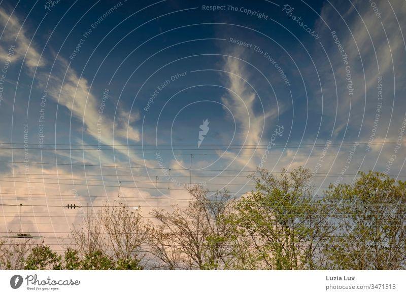 Frühlingshimmel, am Bahnhof Stadt Sonnenschein urban zart schön hell weiss stürmisch Wolken Wolkenspiel Oberleitung grün Bäume Blauer Himmel