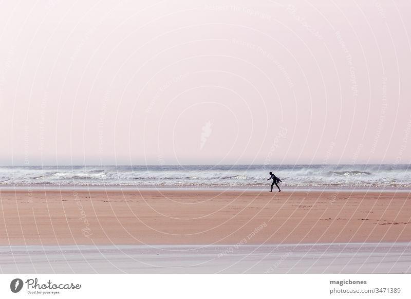 Einsamer Surfer mit einem Surfbrett an einem Strand in Cornwall, UK aktiv Aktivität Abenteuer atlantisch blau Holzplatte Küste Küstenlinie Tag England Spaß