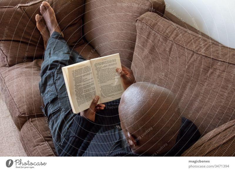 Schwarzer Mann, afrikanischer Ethnie, liest auf dem Sofa 40s Karibik Erwachsener Afrikanisch Amerikaner schwarz Buch Briten lässig Komfort bequem Konzept Liege