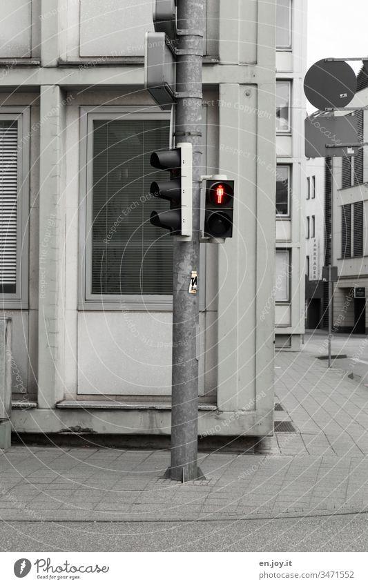 rote Ampel am Straßenrand in der Stadt Ampelmännchen Verkehrszeichen Fußgängerampel stillstehen Stillstand Innenstadt entsättigt Fassade Häuser Gehweg Ecke