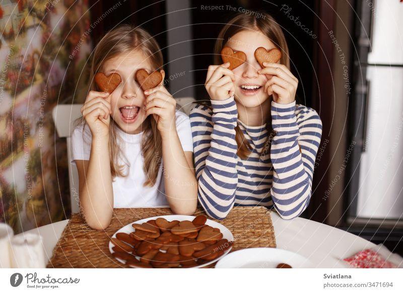 Charmante, lustige und lachende Mädchen halten herzförmige Kekse in der Hand, schließen die Augen und albern herum. Valentinstag und Frauentag niedlich Küche