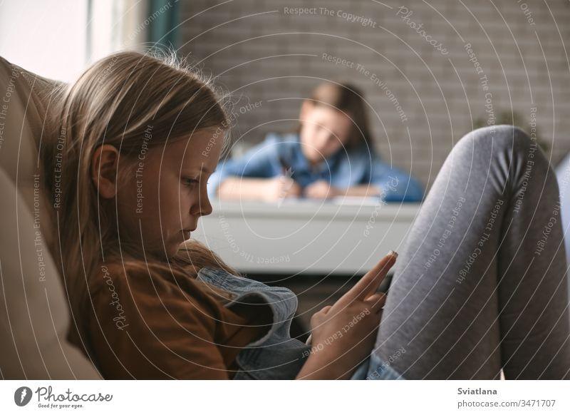 Ein süßes Mädchen spielt am Telefon, während ihre Schwester ihre Hausaufgaben macht. Kommunikation, soziale Distanz während der Quarantäne. Fernunterricht, Online-Bildung