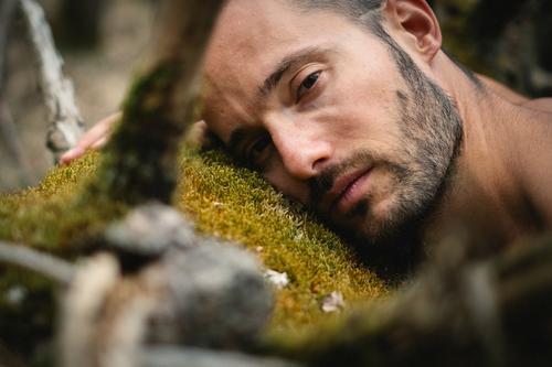 Porträt eines Mannes, der auf einem Baumstamm mit Moos im Wald liegt und traurig, melancholisch, ernst, verletzlich in die Kamera blickt Klima naturverbunden