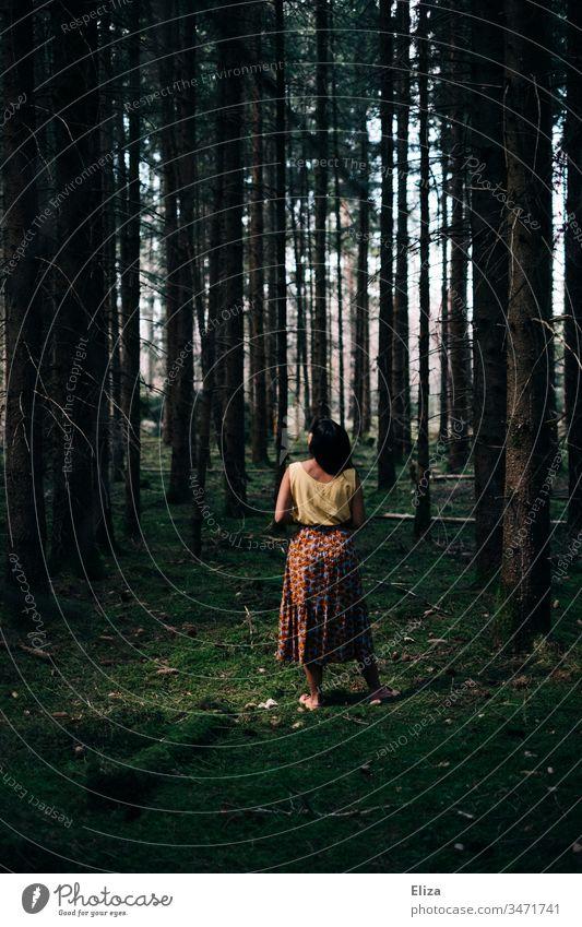 Eine Frau in bunter Sommerkleidung steht zwischen vielen Baumstämmen im Wald auf moosbedecktem Boden Moos Mädchen grün dicht dunkel Sonnenlicht einsam alleine