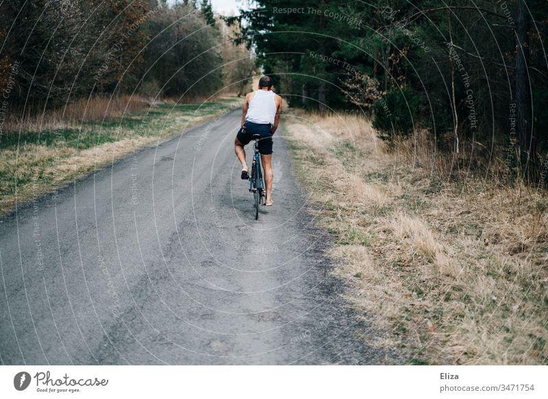 Junger Mann auf einem Fahrrad beim Fahrradfahren auf einer Straße durch den Wald Fahrradfahrer Freiheit Sommer Weg Sport Außenaufnahme Freizeit & Hobby