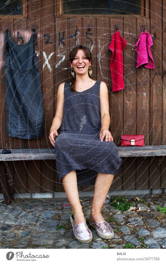 Junge Frau sitzt lachend auf einer Bank, vor einer Garderobe aus Holz, an welcher ein Kleid und Handtücher hängen. Jugendliche Mädchen Mensch Teenager Lifestyle