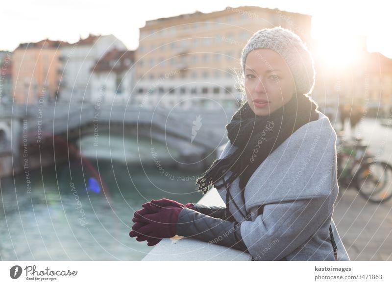 Nachdenkliche Frau an einem kalten Wintertag im Freien. schön Mädchen Porträt Dame Großstadt Ljubljana Lifestyle Schönheit Fluss Sonne attraktiv Kaukasier