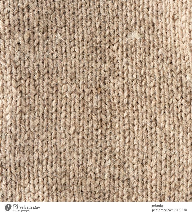 Fragment einer Maschenware aus hellbrauner Schafwolle beige Garn Hintergrund Leinwand Nahaufnahme Stoff Kleidung Bekleidung Farbe Handwerk Dekor dekorativ