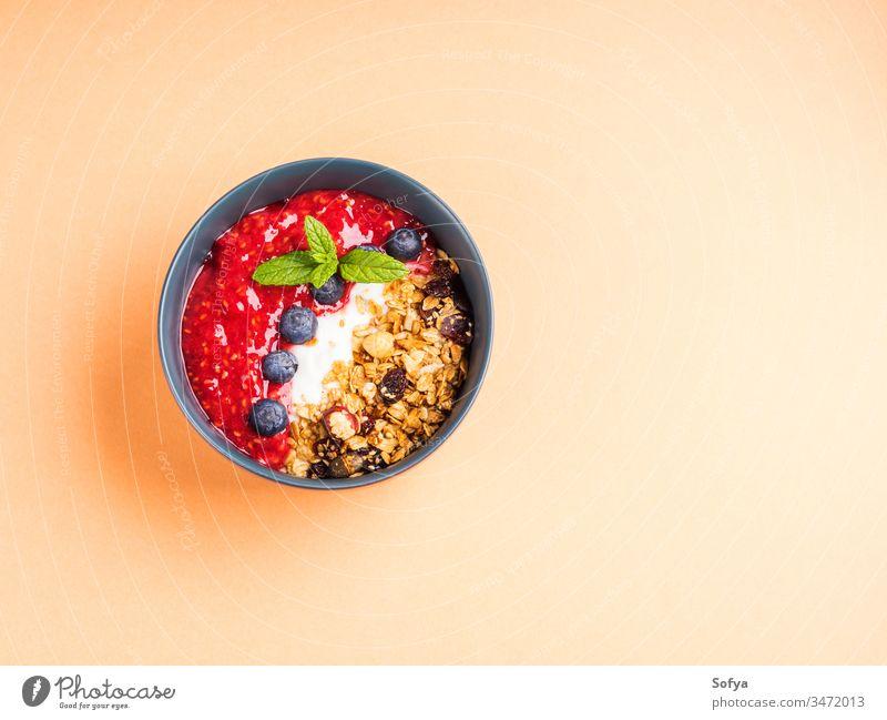 Joghurtschale mit Himbeeren auf Pfirsich-Orange Pastell Müsli Hafer Gesundheit lecker Konzept Smoothie Schalen & Schüsseln Blaubeeren gemischt Hintergrund