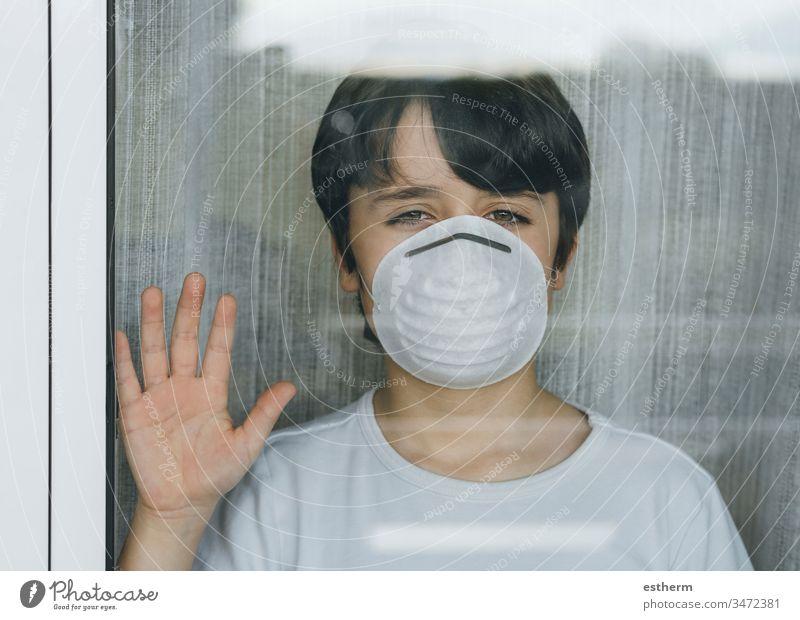 Durch die Coronavirus-Pandemie unter Quarantäne gestelltes Kind mit medizinischer Maske Virus Seuche traurig covid-19 Symptom Medizin Gesundheit Mundschutz