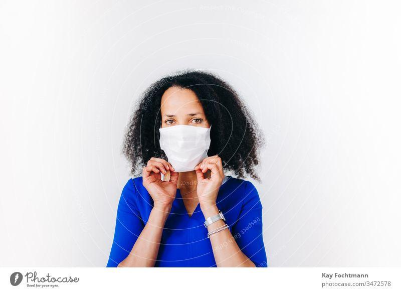 Schwarze Frau, die eine chirurgische Maske aufsetzt Afroamerikaner schwarz Schwarzes Haar blau blaues Hemd Coronavirus covid-19 krause Haare Tag Krankheit