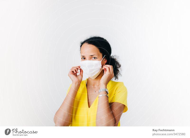 Schwarze Frau, die eine chirurgische Maske aufsetzt Afroamerikaner schwarz Schwarzes Haar blaues Hemd Coronavirus covid-19 krause Haare Tag Krankheit Gesicht