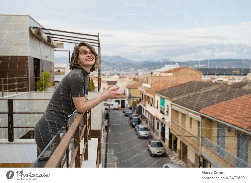Junge Frau auf Koran lobt zur Unterstützung des Gesundheitspersonals Beifall spendend Klatschen Erwachsener Balkon Gemeinschaft Coronavirus Gruß Hände
