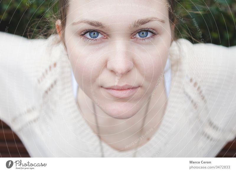 Nahaufnahme eines Mädchens, das ein weißes T-Shirt mit blauen Augen trägt und in ruhiger Pose aufmerksam in die Kamera schaut schön Schönheit blaue Augen