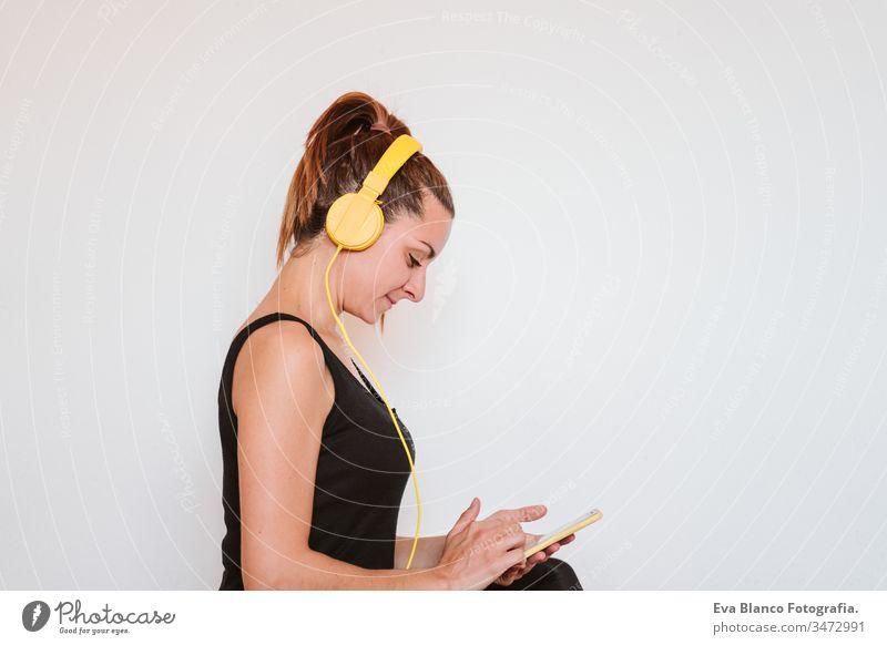Junge Frau, die mit einem gelben Mobiltelefon und einem Headset Musik hört. Sitzt auf einer Yogamatte und entspannt sich nach dem Sport. Gesunder Lebensstil im Haus