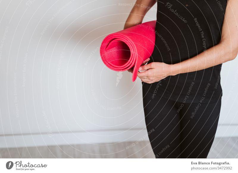 unkenntlich Junge Frau, die zuhört und die Yogamatte hält, bereit zum Üben. Gesunder Lebensstil im Haus Unterlage heimwärts im Innenbereich eine jung Kaukasier