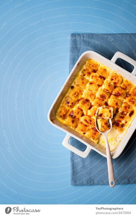 Käse-Gnocchi in keramischer Ofenschale. Italienische Nudeln mit geschmolzenem Käse gebackene Lebensmittel Blauer Hintergrund gekocht Sahnesauce Abendessen
