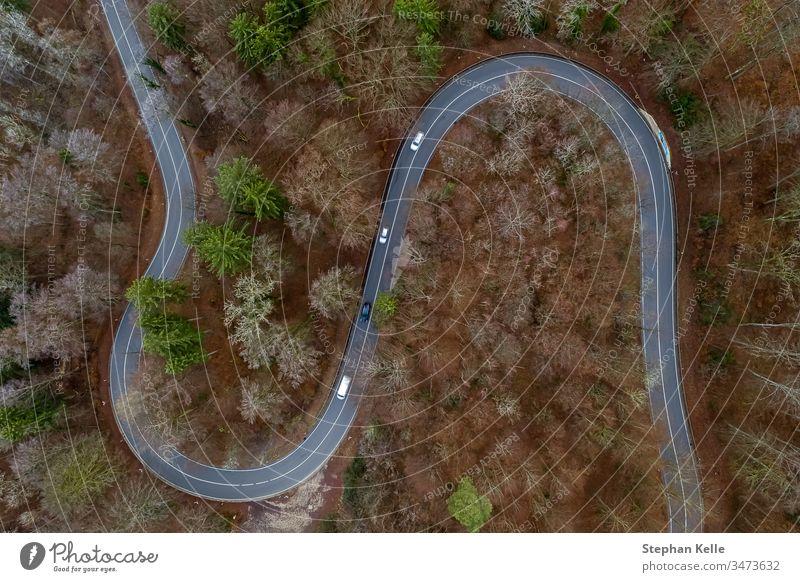 Blick von oben auf eine kurvige Straße von Autos befahren in wäldlicher Landschaft, aufgenommenes Aerial mit einer Drohne Verkehr Kurve wald bäume vegetation